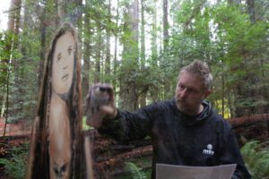 Shane Grammer painting Carrie Fisher mural in wilderness facing camera