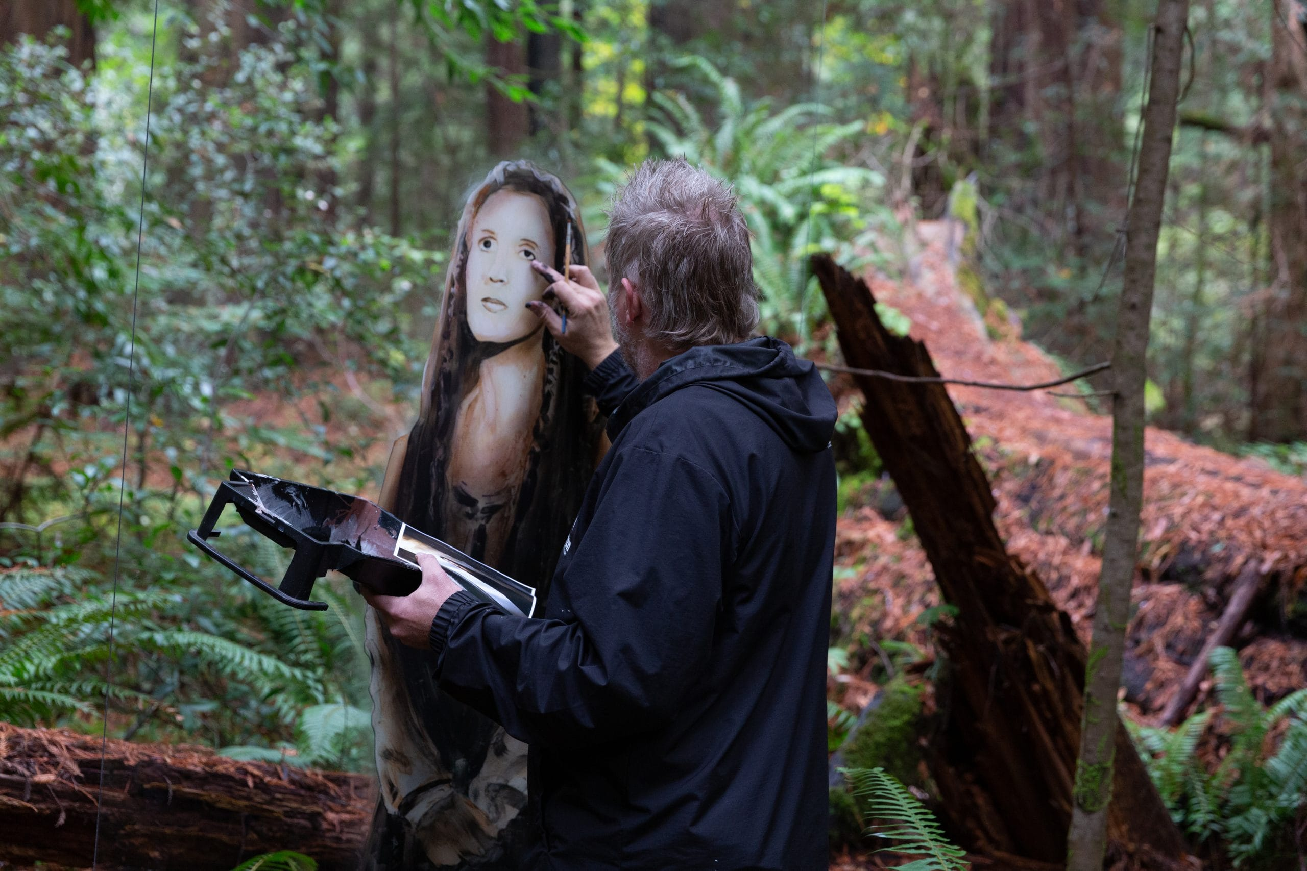 Shane Grammer painting Carrie Fisher mural in wilderness back to camera